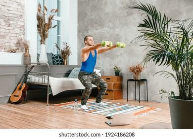 若い男性が自宅でスポーツに出かけ、ラップトップからオンラインでトレーニングします。アスリートはダンベルでしゃがんだり、寝室で映画を見たり、背景にはベッド、花瓶、カーペットがあります。