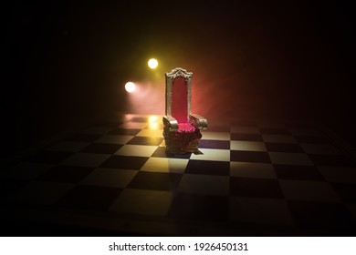 Rote königliche Stuhlminiatur auf Holztisch. Mittelalterlicher Thron auf Schachbrett. Schachbrettspielkonzept von Geschäftsideen und Wettbewerbs- und Strategieideenkonzept. Selektiver Fokus