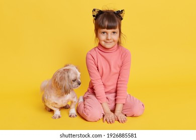Girl with puppy isolated over yellow background, child looking directly at camera with smile, kid wearing rose sweater, pants and hair band with cat's ears, small kid with Pekingese.