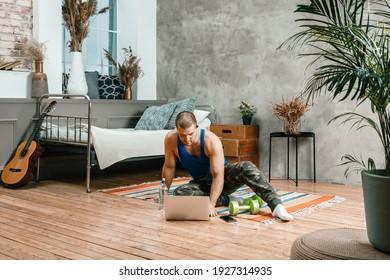 スポーツユニフォームを着た若い男性のクローズアップが休んでいて、家の床に伸びて、映画を見て、ラップトップ、ソーシャルネットワークから勉強しています。学生がうろついている