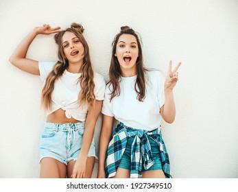 Porträt von zwei jungen schönen lächelnden Hipster-Frauen in den trendigen weißen Sommer-T-Shirt-Kleidern. Sexy sorglose Frauen, die auf Straßenhintergrund aufwerfen. Positive Models, die Spaß haben, sich umarmen und verrückt werden