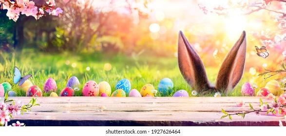 Escena de Pascua abstracta Defocused - Bunny de orejas detrás de la hierba y huevos decorados en campo florido