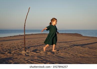 Cute little girl in green dress playing on the beach in a desert island.