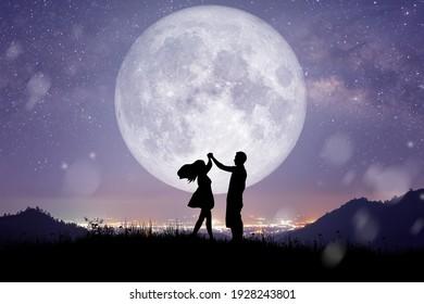 満月の上の天の川の背景と山で踊ったり歌ったりするカップルや恋人の夜の風景のシルエット。