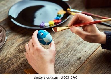女性の手の保護フェイスマスクのイースターエッグ。卵殻にフェイスマスクを描いている女の子。アーティストのワークスペースをクローズアップ