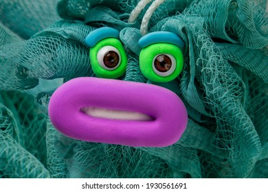 Animated washcloth with big eyes and pink lips. Cartoon plasticine parts of face on thing