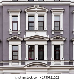 ヨーロッパ、ラトビア、リガの茶色の窓の周りにある8つの窓、白い柱、装飾のグレーパープルアールヌーボー様式の建物のファサードの詳細。1つの窓にはピンクの卵のような形が見えます。