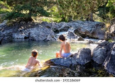 twee jongens op hun rug genieten van een duik in een heldere bergrivier in een rotsachtig, zonovergoten zwembad met rotsen eromheen