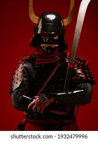 Un joven europeo con un traje tradicional de samurai ronin japonés con una espada katana sobre un fondo oscuro y en la calle. Cosplay y Carnaval