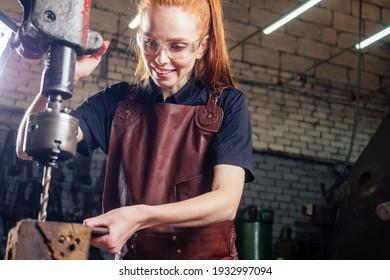 redhaired生姜若いヨーロッパのフェミニスト女性革エプロンを身に着けている鍛冶屋workshop.smallビジネスの強力で独立した概念