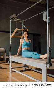 ピラティスキャデラックのベッドに座って、リフォーマーでのフィットネストレーニングルーチン中に休憩している青いスポーツウェアのブルネットの女性。日光のある大きなジムで脇を向いているプロにフィットします。