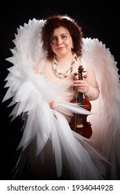 黒の背景にバイオリンと白い天使の羽を持つエレガントなドレスのブルネットの少女。モデル、ヴァイオリニスト、スタジオでポーズをとる女優