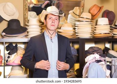 Glücklicher erwachsener Mann probiert westlichen Hut im Einkaufszentrum an