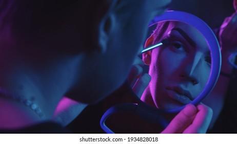 Artista de arrastre - joven aplicando color base en sus ojos - iluminación de neón azul y púrpura