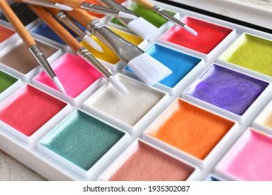 Ein Nahaufnahmebild eines bunten Satzes von Aquarellfarben mit Pinseln.