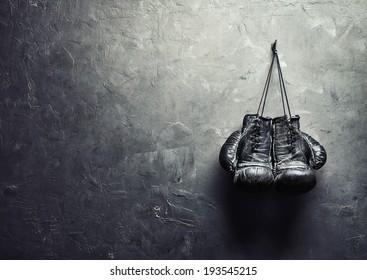 oude bokshandschoenen hangen spijker op textuurmuur met exemplaarruimte voor tekst. Pensioen concept