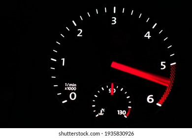 Close up of car dashboard tachometer on blackground. 5000 - 6000 rpm.