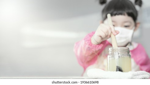 Little Asian girl with face mask  painting water colors during Covid-19 quarantine at home, Kids aged 3 years old.Social distance during quarantine and art concept background.Focus on water glass.