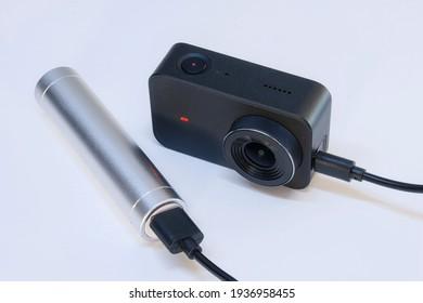 Een compacte action camera voor het maken van video en foto's op een witte achtergrond wordt opgeladen via een powerbank