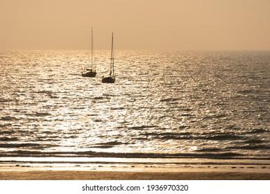 Silueta de veleros al atardecer en una playa en Pléneuf, Côtes d'Armor, Bretaña, Francia