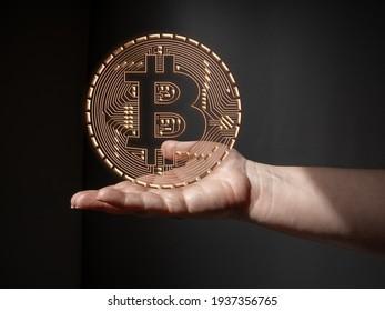 Eine weibliche Hand hält ein goldenes Bitcoin-Logo als Konzept für die Entwicklung von Informationstechnologien und Farmen für den Abbau von Kryptowährungen.
