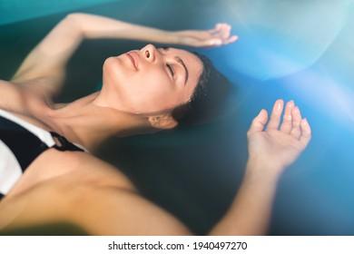 Schöne Frau, die im Tank schwimmt, der mit dichtem Salzwasser gefüllt wird, das in Meditation, Therapie und alternativer Medizin verwendet wird.