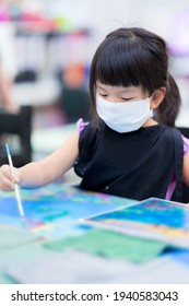 Portrait of cute Asian girl wearing a white cloth face mask. Students are studying art in class. Happy children paint the water on the canvas. Child wears a black apron. Kids is 4 years old.