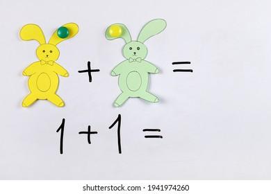 Naučiť deti základom sčítania matematiky pomocou magnetov a postavičiek zajačikov, vyrezaných z papiera, na tabuli, na príklade náučnej detskej hry v matematike