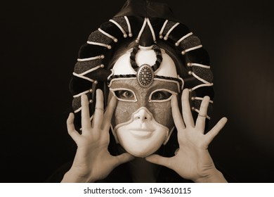 A young blonde girl tries on a fabulous theatrical mask on a dark background