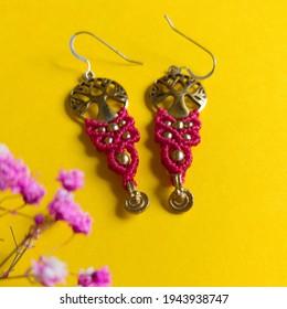 Macramé oorbellen gemaakt van rood gewaxt draad geweven op een levensboom in messing op gele achtergrond.