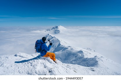 Die einsame Person, die sitzt, schaut weiter auf einen Berg, der in Nebel und Wolken gehüllt ist und dessen Gipfel sichtbar ist. Szenische Landschaftsfoto-Zusammensetzung. Wanderer Trinkwasser in Bergen. Winterabenteuer
