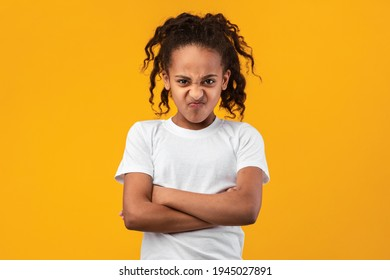 人々の感情、十代の過剰主義の概念。黄色のスタジオの壁に孤立して立って、腕を組んでポーズをとって気分を害した若い黒人少女の肖像画。カメラを見て、手を組んで怒っている女性
