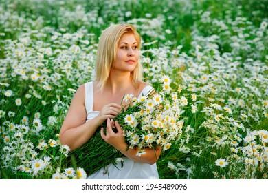 Ein schönes Mädchen in Übergröße mit weißen Haaren in einem Sommerkleid posiert im Freien mit einem Strauß Kamille. Molliges Mädchen auf einer Wiese mit Gänseblümchen bei Sonnenuntergang im Sommer.