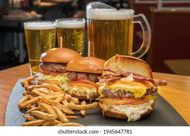 Bacon cheese burger platter with fries at a diner style restaurant with a pitcher of beer.