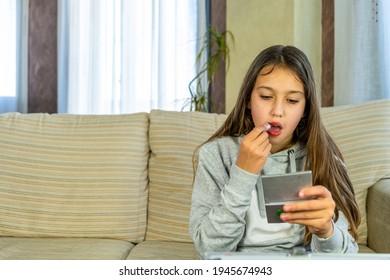 Schönes jugendliches Mädchen, das ihre Lippen malt, die in einem Schminkspiegel in ihrem Wohnzimmer schauen. Wachstumskonzept