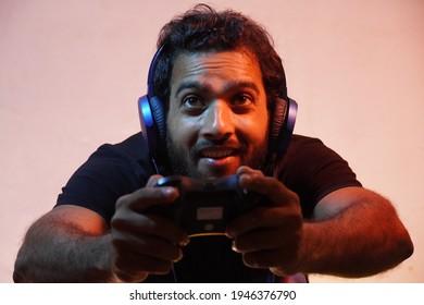 junger Mann, der zu Hause Videospiel mit Joystick spielt und Kopfhörer trägt