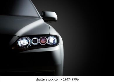 Graue moderne Auto-Nahaufnahme auf schwarzem Hintergrund.