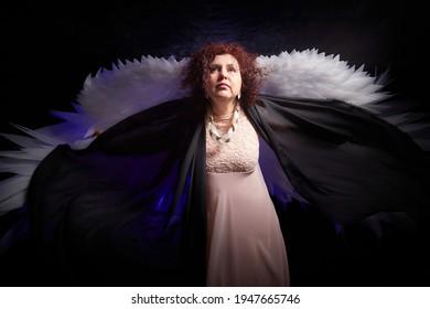 黒の背景に白い翼を持つ邪悪な天使のように見える黒いドレスのブルネットの巻き毛の少女。スタジオでポーズをとるモデルと女優