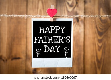Happy Father`s Day message written on old photo on hanging on rope with wooden wall