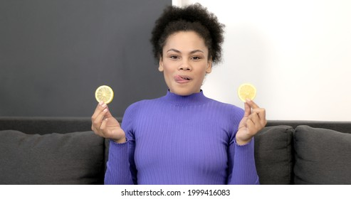 ソファの上の皿からレモンを食べる若いアフリカ系アメリカ人の女の子。酸っぱい果物。健康的な食事。