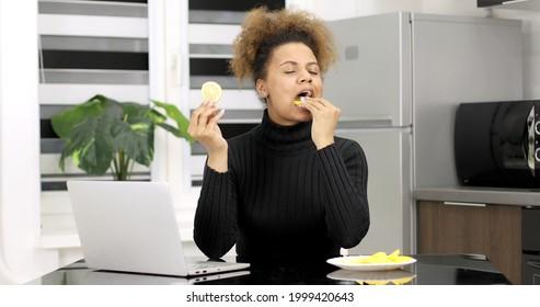 若いアフリカ系アメリカ人の女の子はレモンを食べます。美しい女性の肖像画。酸っぱいレモンを食べながら女の子がしかめっ面。