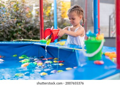 Child Fisher Catching Plastic Toy Fish On Pool Amusement Park Summer Day Little Girl Have Fun On Fishing Carnival Festival Entertainment For Children