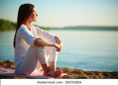 Seitenansicht der ruhigen Frau, die auf Sandstrand gegen blauen Himmel draußen sitzt