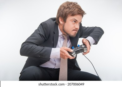 Sehr aufgeregter gutaussehender Geschäftsmann in perfektem schwarzen Anzug, der große Anstrengungen unternimmt, um ein Videospiel zu gewinnen