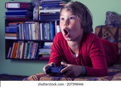 Junge Teenager mit Fernbedienung in der Hand, die eine Videospielkonsole spielt.