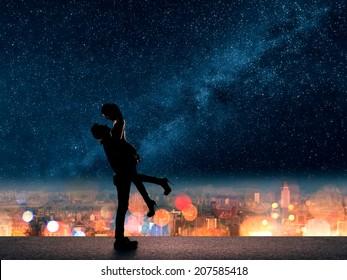 Silhouet van Aziatische paar, man houdt zijn vriendin boven de stad in de nacht onder de sterren.