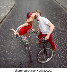 Young loving couple kissing on the bicycles in the city