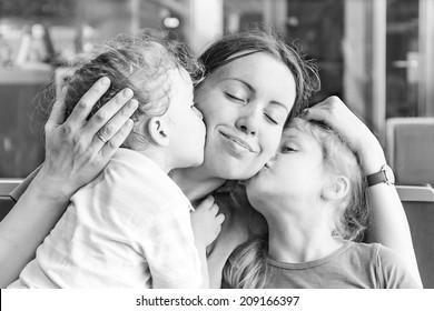 Zwei Töchter küssen ihre glückliche Mutter