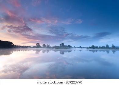 Восход туманного неба отражается в реке в туманное утро