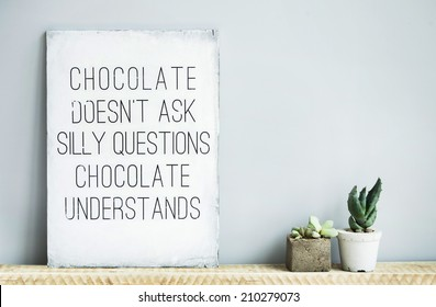 old wooden rustic poster with quote about chocolate with succulents in concrete pots. Scandinavian style home decoration.